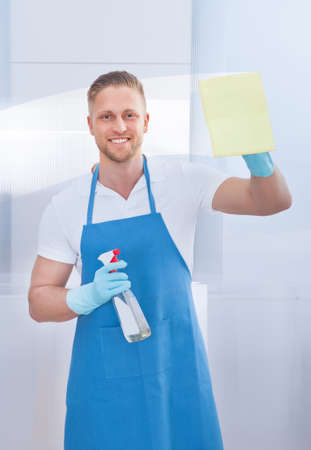 Friendly smiling male cleaner cleaning a pane of glass with a spray bottle and cloth in an office building photo