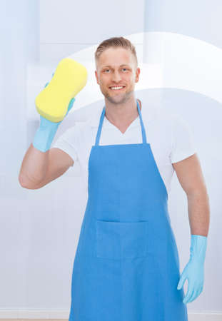 Male janitor using a sponge to clean a window in an office wearing an apron and gloves as he works photo