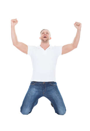 Excited man cheering in jubilation dropping down on his knees with his fists raised in the air as he celebrates a success  on white
