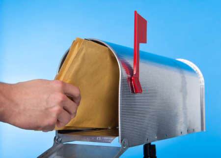 Man opening his mailbox to remove mail inside  close up of his hand on the open door against a blue sky photo