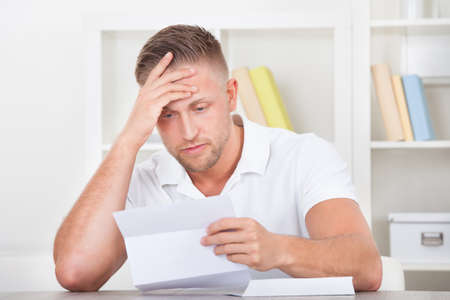 worried businessman: Businessman sitting in an office reacting in shock to the contents of a letter that he is reading raising his hand to his mouth