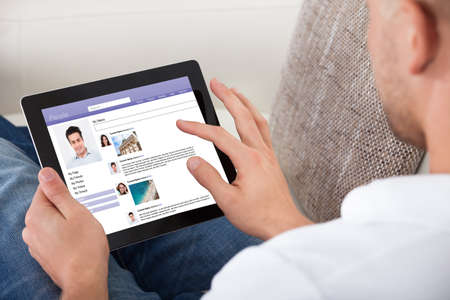 viewers: Man looking at personal profiles or comments left by viewers on a tablet computer navigating the touch screen with his finger  over the shoulder view of the screen