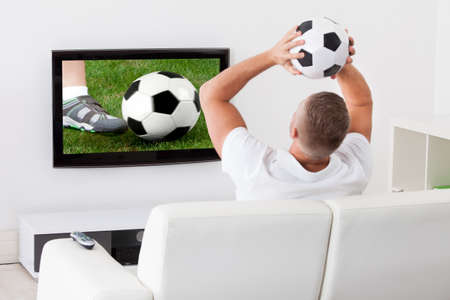 soccer fan: Excited soccer fan watching a game on television holding a soccer ball above his head as he sits on a comfortable sofa in his living room