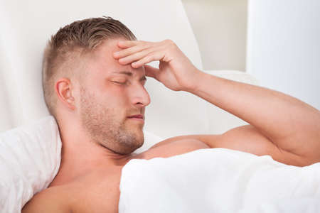 overindulgence: Man waking up with a nasty headache from overindulgence or illness wincing in pain and raising his hands to his head Stock Photo