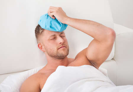 throbbing: Man nursing a hangover after a heavy night of partying holding an ice pack to his forehead with his eyes closed on pain against the throbbing