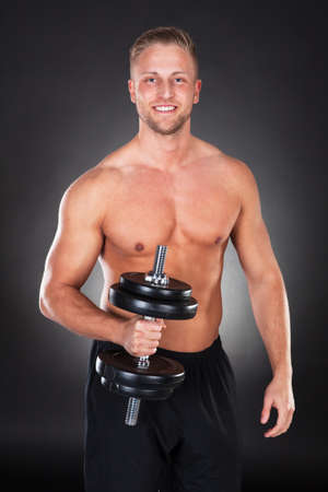 Athletic muscular shirtless young man lifting weights in the gym standing smiling at the camera in a health and fitness concept photo