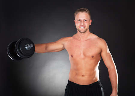 Muscular fit young man working out with weights standing smiling at the camera with a weight held in his hand above his head on a dark background in a health and fitness concept photo