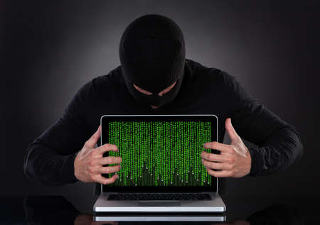 furtively: Hacker in a balaclava standing in the darkness furtively stealing data off a laptop computer or inserting spyware in an online security and risk concept