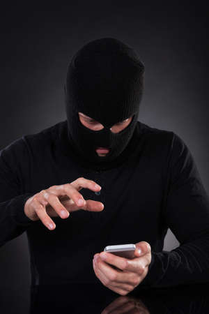 Thief in a balaclava and black outfit standing in the darkness trying to access a stolen mobile phone or a terrorist activating a bomb remotely