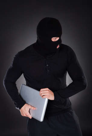 clandestine: Thief stealing a laptop computer creeping furtively through the darkness as he makes his getaway  conceptual of data and identity theft