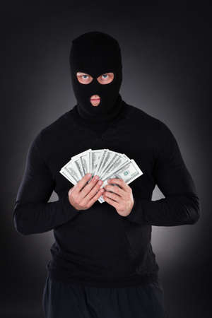 loot: Criminal in a balaclava holding a fistful of money  conceptual of the loot from a robbery  bribe  corruption  coercion  payoff  ransom or mob protection money