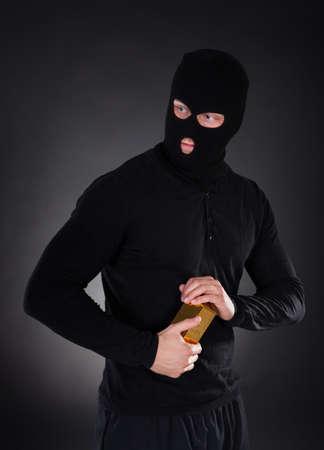 lingotes de oro: Ladrón disfrazado con un pasamontañas negro que sostiene una barra del lingote de oro como él hace su escapada de un atraco con el botín en la oscuridad