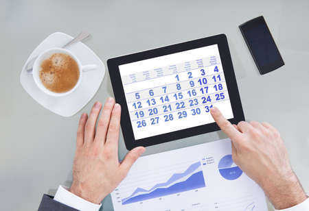Close-up Of Hand Pointing At Calendar Shown On Digital Tablet Stock Photo - 26835422