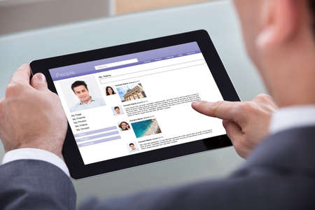 Close-up Of Man Using Social Network On Digital Tablet photo