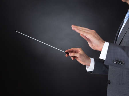 conducting: Close-up Of Orchestra Conductor Hands Holding Baton Over Black Background