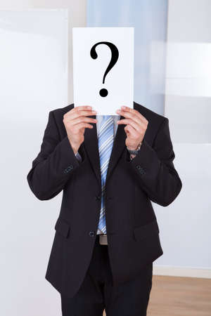 Young businessman holding paper with question mark in front of face at office photo
