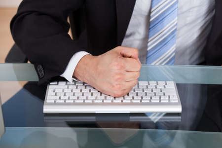 Midsection of businessman pounding fist on keyboard at office desk photo