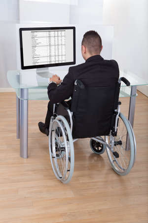 Rear view of businessman on wheelchair using computer in office photo