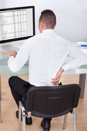 Rear view of young businessman with backache using computer at office desk