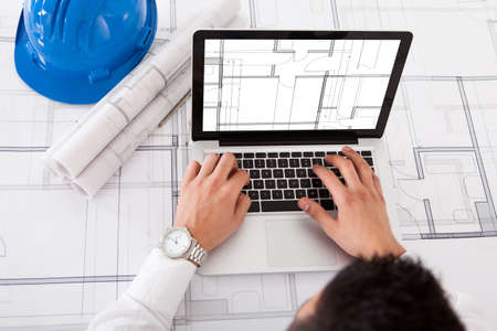Cropped image of male architect using laptop in office photo