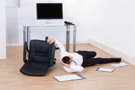 Full length of young businessman fallen from office chair photo