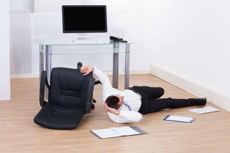 Lunghezza completa di giovane uomo d'affari caduto da sedia per ufficio Archivio Fotografico - 26835455