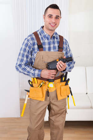 Full length portrait of confident male repairman holding drill machine in living room photo