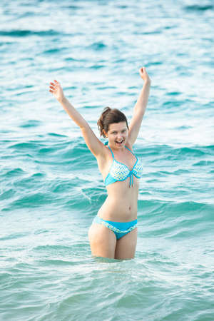 standing water: Portrait of bikini woman with arms raised standing in ocean at beach Stock Photo