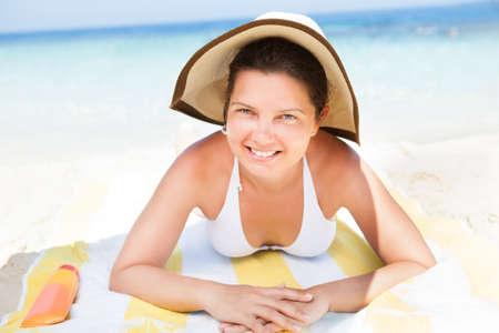 Portrait of smiling woman in bikini top lying on beach towel at seashore photo