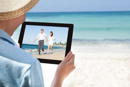 Cropped image of woman watching video on digital tablet at beach photo