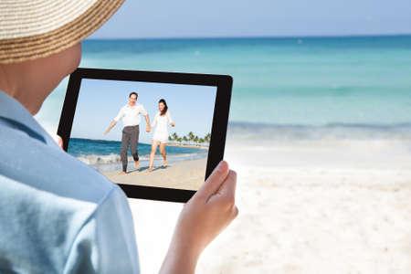 mujer mirando el horizonte: Recorta la imagen de la mujer viendo el video en la tableta digital en la playa