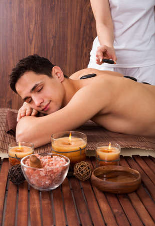 Young man receiving Lastone therapy from massager in spa photo