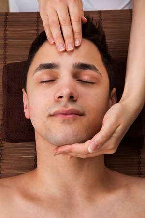 High angle view of young man receiving head massage from massager in spa Stock Photo - 26835487