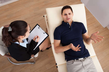 High angle view of male patient communicating while psychologist writing notes on clipboard in clinic