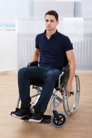 Full length portrait of young handicapped man sitting on wheelchair at home