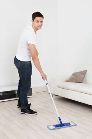 mopping: Full length of young man mopping floor at home