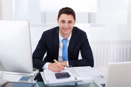 Portrait of smiling businessman calculating tax at desk in office Stock Photo