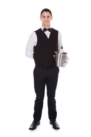 Full length portrait of confident waiter holding champagne bottle in cooler over white background photo