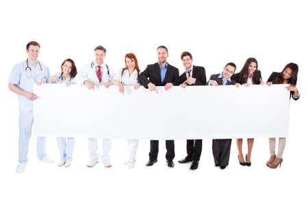 Doctors and managers showing empty banner. Isolated on white photo
