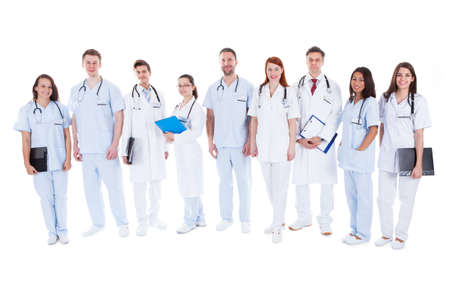 nursing staff: Large diverse group of doctors and nurses in uniform standing in a line holding files of patient records and wearing stethoscopes  isolated on white