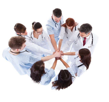 Doctors and nurses stacking hands. Isolated on white photo