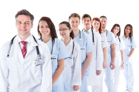 Long receding line or queue of smiling doctors and nurses in white uniforms wearing stethoscopes around their necks isolated on white photo