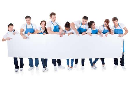 mujer limpiando: Numeroso grupo diverso de limpiadores o conserjes se usan delantales, con un cartel blanco en blanco con copia espacio para el texto aislado en blanco Foto de archivo