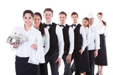 meseros: Gran grupo de camareros y camareras se colocan en fila. Aislados en blanco
