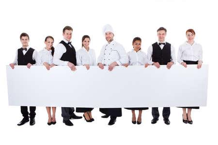 Gran grupo de personal de la cocina, con un cartel en blanco con copyspace para el texto que incluye una anfitriona camareros camareras de chef y sumiller aislado en blanco Foto de archivo