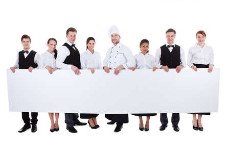Large group of catering staff holding a blank banner with copyspace for your text including a chef  waiters  waitresses  hostess and wine steward  isolated on white Stock Photo