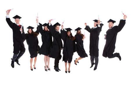 mortero: Grupo regocijo feliz de graduados multiétnicas saltando en el aire que anima en la celebración de la finalización con éxito de sus estudios académicos aislados en blanco