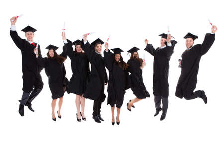 Happy rejoicing group of multiethnic graduates leaping in the air cheering as they celebrate the successful completion of their academic studies  isolated on white Stok Fotoğraf