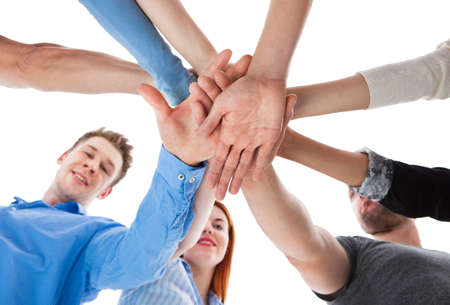 Low angle view of people stacking hands together. Isolated on white photo