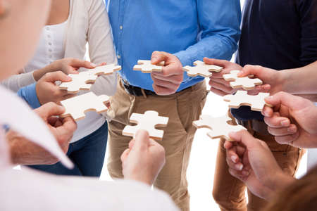 Hoge hoek van mensen verbinden puzzelstukjes op witte achtergrond